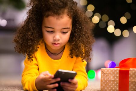 Not Christmas mood. Little afro girl with cellphone ignoring Xmas holiday and gifts, empty space