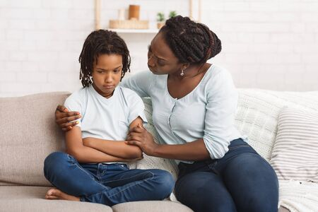 African Mother Apologizing To Her Offended Daughter After Quarrel On Sofa At Home Фото со стока