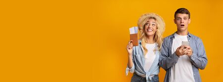 Online credit concept. Frustrated guy checking his bank balance with smartphone, while his girlfriend dreaming about vacation, yellow background Reklamní fotografie