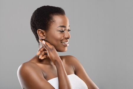 Spa Facial Concept. Beautiful african american girl touching her soft skin on cheek, enjoying result of beauty treatment, grey background.