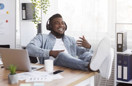 Break at work. Joyful african american businessman listening music in headphones and playing virtual guitar, relaxing at workplace in office.