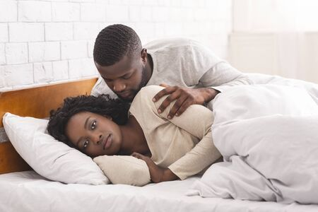 Female Sexual Dysfunction Concept. Woman ignoring husband in bed, refusing to make love.