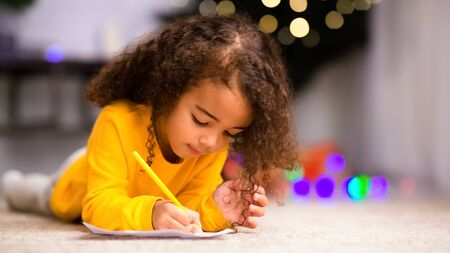 Letter to Santa. Cute african little girl writing on floor near decorated Christmas tree at home, panorama, empty space