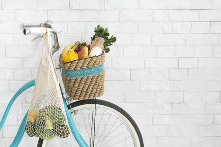 Retro bicycle with fresh products over white bricks wall background, copy space