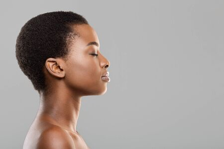 Natural beauty concept. Side view portrait of young beautiful afro woman with flawless skin standing with closed eyes over gray background, copy space