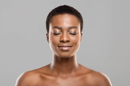 Naked beauty. Portrait of beautiful nude african american girl with closed eyes, natural makeup and perfect skin