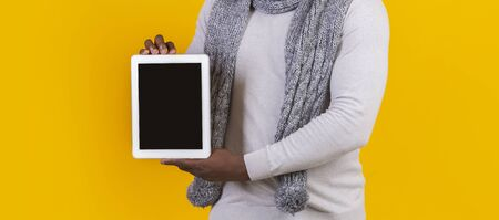 Close up of blank digital tablet screen holding by afro man over yellow background, panorama