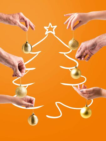 Christmas time. Family members decorating virtual Xmas tree with golden balls, orange studio background