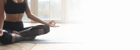 Body of well fit sporty girl sitting at lotus pose, meditating at home, panorama with free space