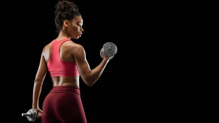 Black fitness lady doing workout with dumbbells, back view, black studio background, panorama with copy space