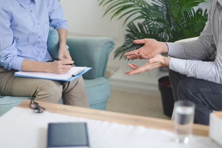 Therapist woman making notes while patient man speaking, session at private psychologist, cropped, free space