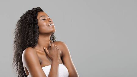 Body care concept. Pleased beautiful black woman enjoying touching her soft skin, standing wrapped in towel after spa treatment over gray background 版權商用圖片
