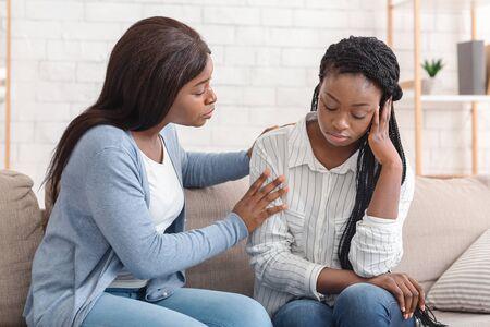 Amistad y apoyo. Compasiva chica negra consolando a su amigo molesto, tranquilizándola después de la ruptura con su novio, sentada en el sofá en casa.