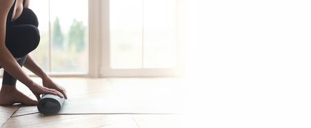 Girl starting her day with meditation, unrolling yoga mat at fitness studio, cropped, panorama with copy space 版權商用圖片