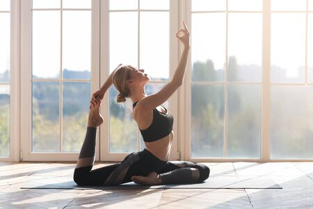 Harmony, balance, health concept. Peaceful girl practicing yoga at home, panoramic window background, copy space