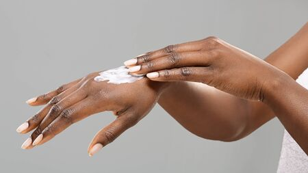Skin nutrition. Hands of unrecognizable afro woman with applied body lotion, panorama with free space Stock fotó