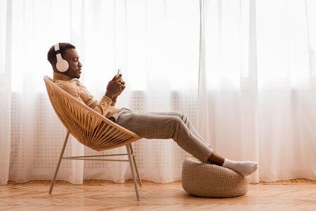 Fin de semana. Hombre negro relajado en auriculares inalámbricos con teléfono móvil escuchando audiolibros sentado en una silla moderna contra la ventana interior