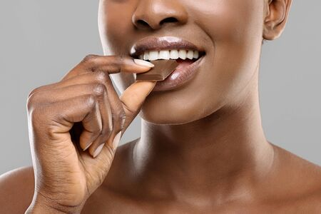 Closeup portrai of Black Woman With White Healthy Teeth Biting Milk Chocolate Slice Over Gray Background, Crop
