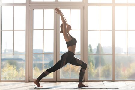 Profile photo of athletic young woman practicing yoga at home over big panoramic window, empty space 版權商用圖片