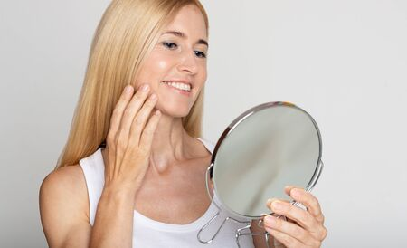 Skincare concept. Happy woman applying cream and looking at mirror over grey background