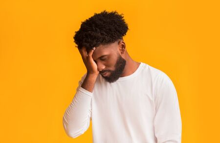 Upset black man covering face with hand, disappointed or stressed, orange studio background, copy space Stock Photo