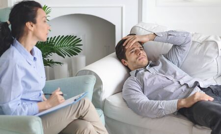 Desperate upset man having private therapy at psychologist office, laying on sofa, touching his head, listening to doctor, empty space