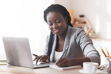 Empresaria negra que trabaja en la oficina, escribiendo en la computadora portátil y tomando notas, espacio libre Foto de archivo