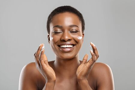 Face care. Attractive african american woman applying moisturizer cream on her cheeks and sincerely smiling, gray background with free space Фото со стока - 134668825