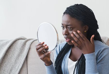 Anti-wrinkle skin care. Disappointed black woman looking to mirror and touching her face while sitting on couch at home