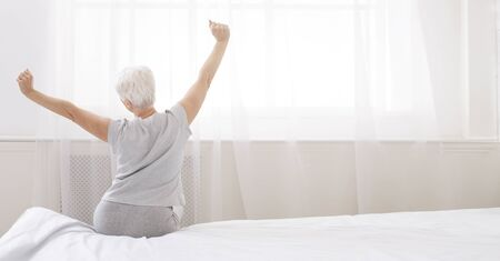 Good morning, world. Well slept senior woman stretching with arms raised on bed, back view, panorama, free space