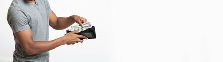 Finance, investment and money saving. African man showing full wallet with dollar banknotes, white panorama background with free space Banco de Imagens