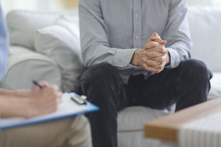 Psychologist taking notes while conversation with patient at psychotherapy session, close up Stock Photo
