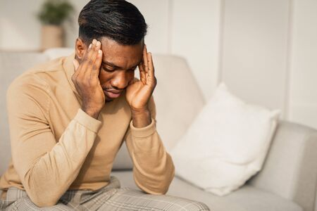 Unhappy Black Guy Suffering Having Severe Headache Massaging Temples Sitting On Couch At Home. Free Space Reklamní fotografie