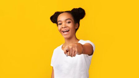 We Need You. Cheerful african american teen girl pointing finger at camera, free space, yellow background