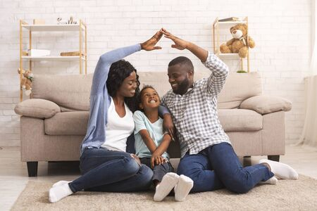 Family care and protection. Black parents making symbolic roof of hands above their little daughters head, sitting together on floor at home