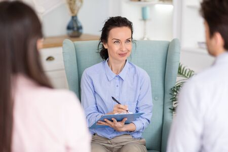 Psychologist listening to couple, asking questions and taking notes at her private clinic Stockfoto