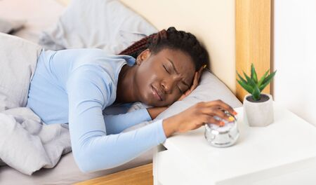 Afro Lady Turning Off The Alarm-Clock Having A Hard Time Waking Up In The Morning Lying In Bed At Home Reklamní fotografie
