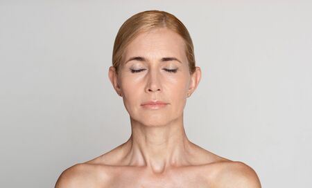Beautiful middle-aged woman with bare shoulders and closed eyes over grey studio background