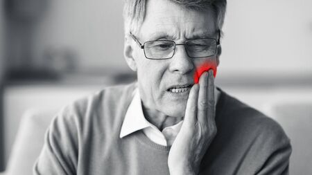 Aching Tooth. Senior Man Suffering From Toothache Touching Red Pain Zone Sitting On Couch Indoor. Panorama, Black-And-White