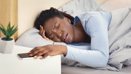 Difficulty Waking Up. African American Lady Having Headache Turning Off Alarm-Clock On Smartphone Lying In Bedroom Indoor, Panorama Reklamní fotografie