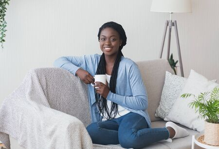 Portrait of attractive african american woman sitting on sofa with cup of coffee and smiling at camera, free space