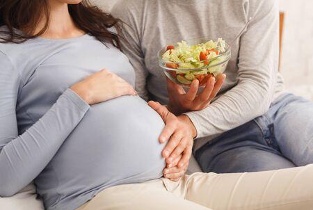 Dieta y nutrición durante el embarazo. El esposo cariñoso preparó una ensalada de verduras frescas para su esposa embarazada y tocó tiernamente su vientre en la cama en su casa. Foto de archivo