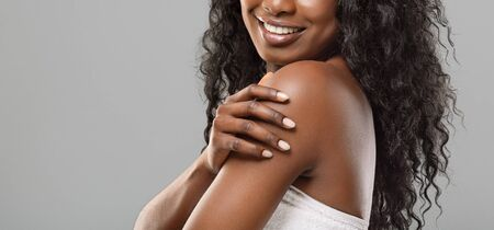 Spa procedures for body. Unrecognizable black woman enjoying her smooth soft skin over grey background, panorama with empty space