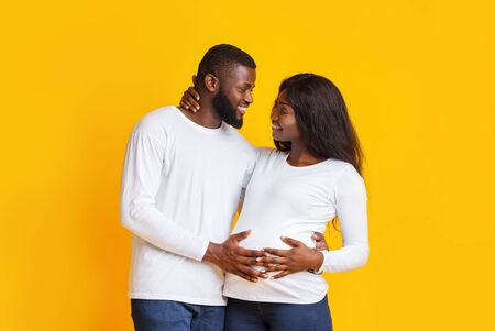 Cheerful back pregnant couple having funny conversation over yellow background, making plans Foto de archivo - 134768376