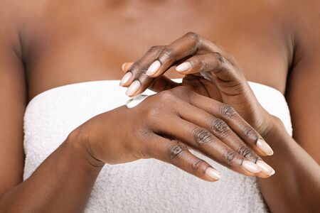 Unrecognizable black female applying rich cream to her hands, standing wrapped in white bath towel, closeup