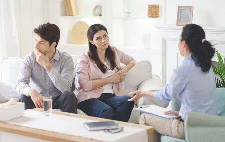 Sad married man and woman attending couple counseling session, wife listen to therapist, husband looking aside Stock Photo