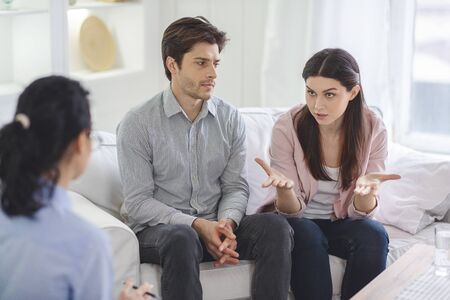 Indignant young woman blaming her husband sitting next to her during family therapy