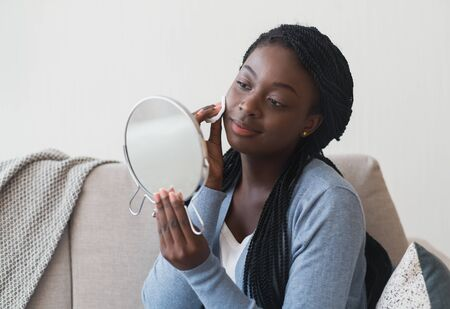 Daily Skincare Routine. Young afro girl looking in mirror and cleaning face with cotton pad, while sitting on couch at home, free space Reklamní fotografie