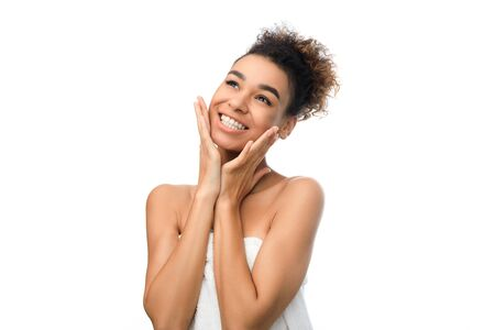 Soft touch. Afro woman touching her velvet skin, enjoying result of beauty treatment, white background