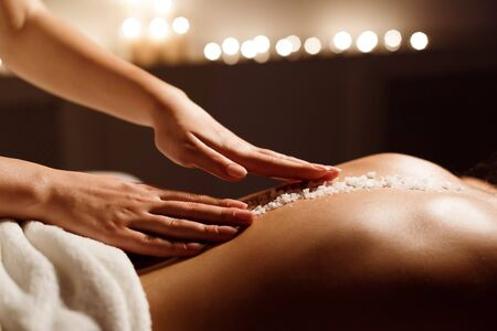 Spa concept. Woman receiving salt back massage, therapist hands closeup Фото со стока - 134768823